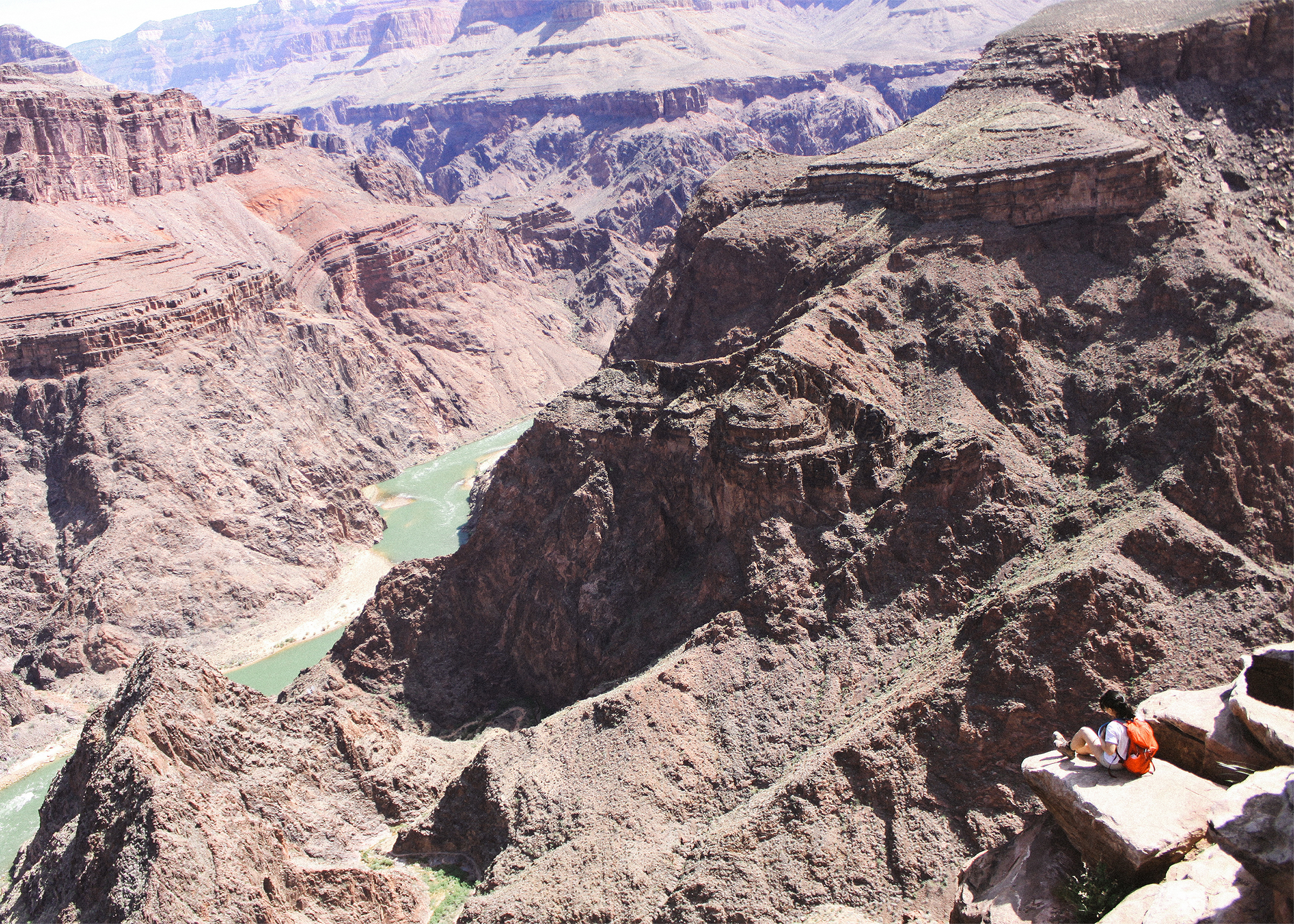 Jennifer sitting at Plateau Point with the Colorado River beneath her