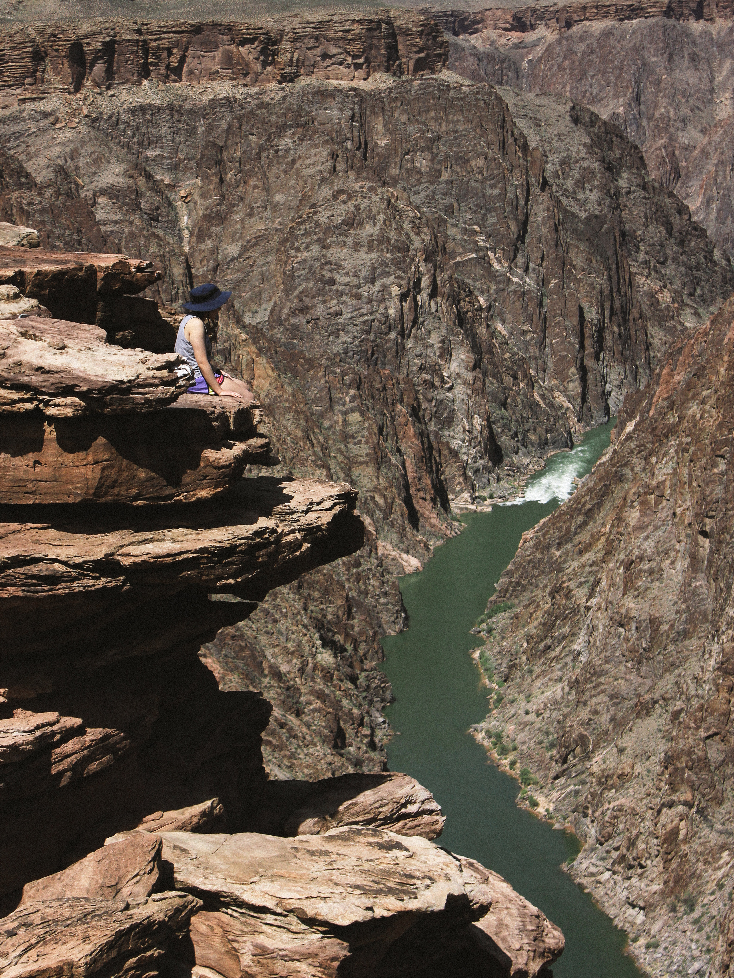 Vivian sitting at Plateau Point with the Colorado River beneath her.