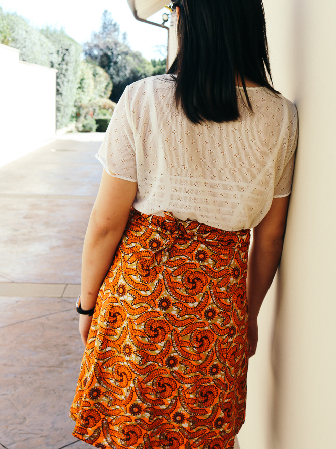Vivian in a laced top and knee length wrap skirt.