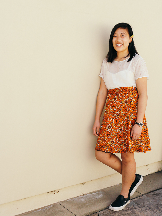 Vivian in a laced top, knee length wrap skirt, and leather sneakers.