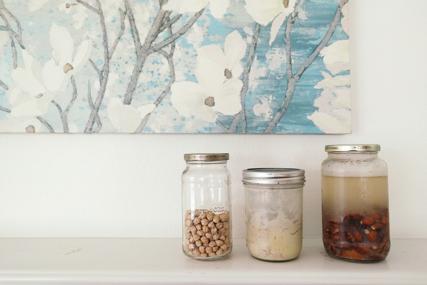 Cover photo with garbonzo beans, hummus, and soaked almonds, all in glass jars.