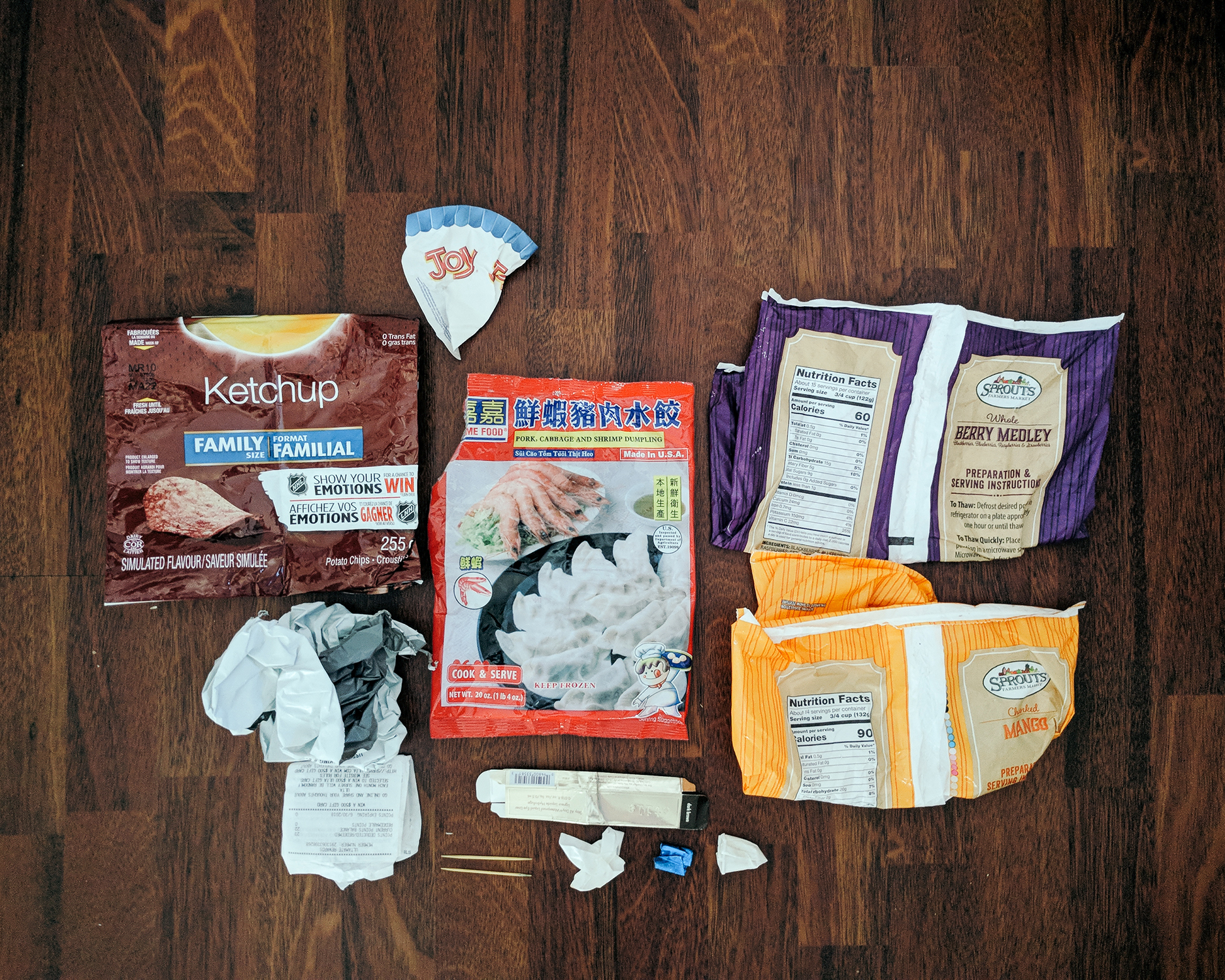 Packaging from Lay's Ketchup chips, clothes from online, receipts, wax-lined paper from an ice cream cone, Asian dumplings, eyeliner, toothpicks, sample cup, gum wrappers, and frozen fruits